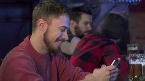 El individuo mecanografía en su smartphone en el pub imagen de archivo libre de regalías