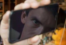 El individuo mira la pantalla de un smartphone negro, con la reflexión de las miradas de la pantalla un ojo en la cámara Fotografía de archivo