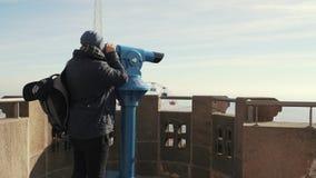 El individuo mira a través de los prismáticos de visión de una altura de la ciudad almacen de video