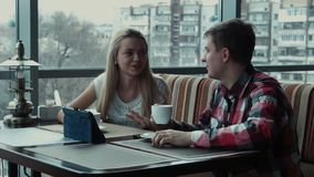 El individuo muestra algo en el panel táctil a la muchacha en café almacen de video