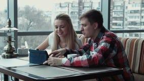 El individuo muestra algo en el panel táctil a la muchacha en café metrajes