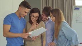 El individuo muestra a sus compañeros de trabajo algo divertido en su diario