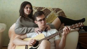 El individuo para la muchacha toca la guitarra almacen de video