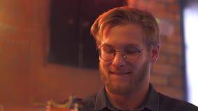 El individuo pelirrojo en vidrios con una barba toma un cóctel metrajes