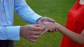 El individuo pone el anillo en el finger de su novia metrajes