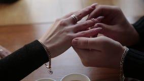 El individuo pone a su novia en el anillo de bodas del finger en un café almacen de metraje de vídeo