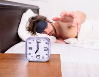 El individuo prefiere se relaja en oscuridad Despertador en fondo barbudo sin afeitar soñoliento de la máscara de ojo del sueño d fotografía de archivo