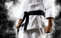 El individuo presenta en el kimono blanco con la correa negra foto de archivo