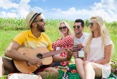El individuo que escucha de la gente joven que toca la guitarra agrupa día de verano de los amigos Foto de archivo