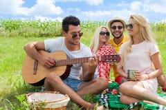 El individuo que escucha de la gente joven que toca la guitarra agrupa día de verano de los amigos Fotografía de archivo