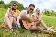 El individuo que escucha de la gente joven que toca la guitarra agrupa día de verano de los amigos Imagen de archivo libre de regalías