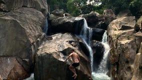 El individuo que salta del acantilado rocoso en la cascada en Vietnam metrajes