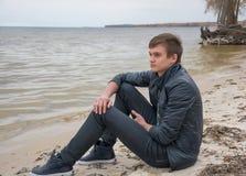 El individuo que se está sentando en la orilla del mar del otoño Fotografía de archivo libre de regalías