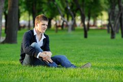El individuo que se sienta en la hierba Fotografía de archivo