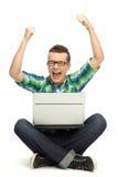 El individuo que usaba la computadora portátil con los brazos levantó Imagenes de archivo