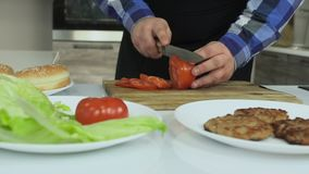 El individuo regordete cocina las hamburguesas caseras en su cocina Tomates de los cortes del hombre en la tabla de cortar Forma  metrajes