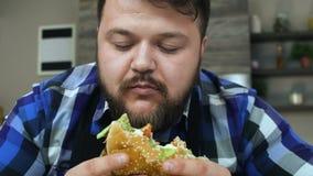 El individuo regordete con una barba muerde un pedazo de hamburguesa La comida es muy deliciosa El individuo regordete está alegr almacen de metraje de vídeo