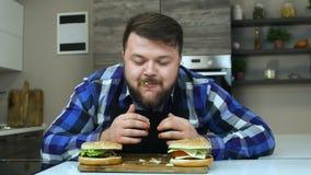 El individuo regordete goza de su hamburguesa La salsa de tomate corre de los fingeres del hombre El hombre gordo con una barba m metrajes