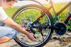 El individuo repara la bicicleta reparación de cadena unratitude en el camino, viaje, primer del ciclista fotografía de archivo libre de regalías