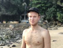 El individuo rubio de piel clara en un casquillo en la playa sin broncea sin sonrisas de la prendas de vestir exteriores foto de archivo libre de regalías