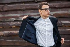 El individuo saca su chaqueta Elegante, hermoso, hombre en el traje clásico, presentando cerca de la pared de madera foto de archivo