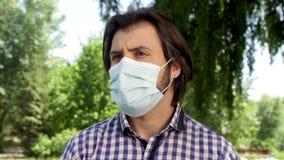 El individuo se está colocando en parque y máscara que lleva en cara que él es enfermo y de mirada a los left and right pocas vec almacen de metraje de vídeo