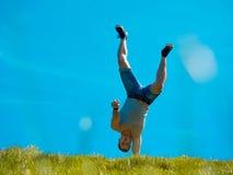 El individuo se está colocando por un lado Cielo azul Debajo de la hierba verde Fotos de archivo
