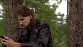 El individuo se está sentando con el teléfono en el bosque metrajes