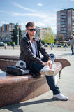 El individuo se está sentando en la calle imagen de archivo