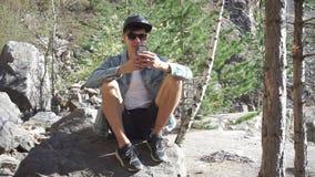 El individuo se está sentando en una roca metrajes
