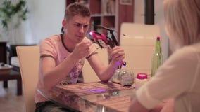 El individuo se sienta con el blonde, saca el anillo de bodas del helicóptero del juguete y la deja almacen de video