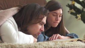 El individuo soñoliento y la muchacha cansados que mienten en el piso y leen el libro, después el hombre y la mujer se caen dormi almacen de metraje de vídeo