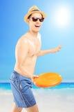 El individuo sonriente en la natación pone en cortocircuito frizbee que lanza, en una playa Foto de archivo