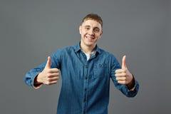 El individuo sonriente vestido en una camisa de los vaqueros mantiene ambos pulgares para arriba el estudio en el fondo gris fotos de archivo