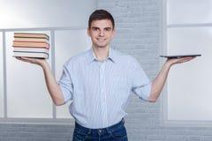 El individuo sostiene una tableta moderna y una pila de libros en equilibrio fotografía de archivo libre de regalías