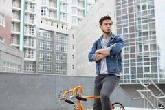 El individuo va a la ciudad en una bicicleta en chaqueta de los tejanos hombre joven una bici anaranjada del arreglo fotografía de archivo