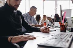 El individuo vestido en ropa casual del estilo de la oficina est? trabajando con los documentos que se sientan en el escritorio c imagen de archivo