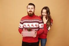El individuo vestido en suéter rojo y blanco con los ciervos lleva a cabo un regalo de Navidad en sus manos y una muchacha mira h foto de archivo