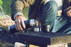 El individuo vierte té de la baya de un termo en naturaleza El concepto de reconstrucci?n al aire libre foto de archivo libre de regalías