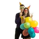 El individuo y la muchacha agradables sonrientes con los conos en sus cabezas se sostuvieron cerca de los maniquíes y de los glob Fotos de archivo libres de regalías