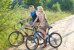 El individuo y la muchacha en bicicletas en el camino rural en el día de verano Fotografía de archivo