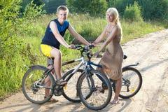 Adolescentes en bicicletas en el camino rural en el día soleado del verano Fotos de archivo libres de regalías
