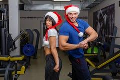 El individuo y la muchacha, en los sombreros de la Navidad, colocándose uno al lado del otro, mostrando apagado sus músculos fotografía de archivo