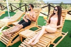 El individuo y la muchacha están descansando sobre sunbeds y miran a la izquierda Sostienen los vidrios de cócteles en manos La m imagenes de archivo