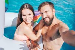 El individuo y la muchacha están en piscina Ella está en colchón de aire El hombre joven sostiene la cámara Lo miran y sonríen Gr imágenes de archivo libres de regalías