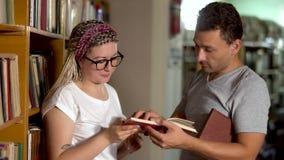 El individuo y la muchacha están hablando en la biblioteca almacen de metraje de vídeo