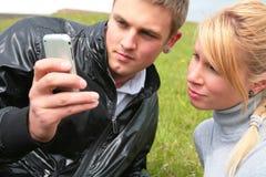 El individuo y la muchacha miran el dispositivo Imagen de archivo libre de regalías