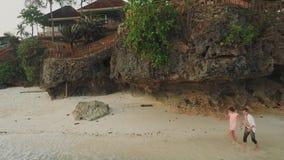 El individuo y una muchacha están corriendo a la costa con las casas Tiempo de la tarde La naturaleza hermosa de las Filipinas Si almacen de video