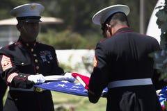 El infante de marina dobla la bandera en la ceremonia conmemorativa para el soldado caido de los E.E.U.U., PFC Zach Suarez, misió Fotografía de archivo