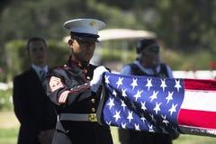 El infante de marina dobla la bandera en la ceremonia conmemorativa para el soldado caido de los E.E.U.U., PFC Zach Suarez, misió Foto de archivo libre de regalías
